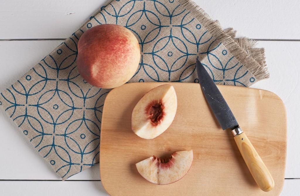 Couteaux Pallares Solsona sur une planche en bois avec des pèches